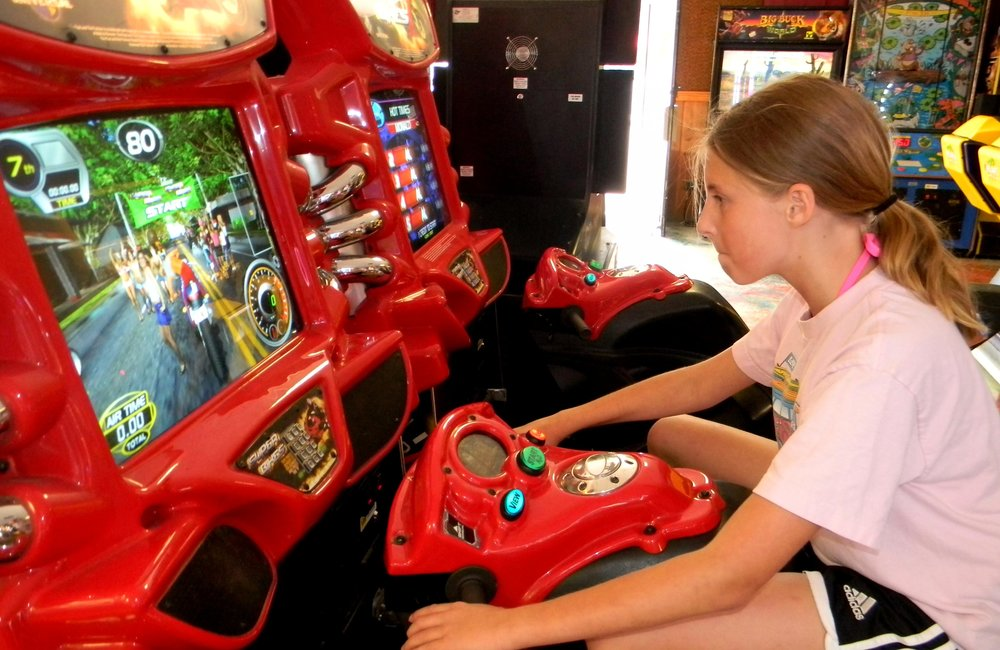 "Maddie Ballerini, 11, of Harwinton, Connecticut, concentrates during her high-speed adventure on the ""Super Bikes"" at the Fun World arcade in Lake George. The arcade offers 100 games for people who like video, pinball and athletic challenges. Jeff Wilkin photo"