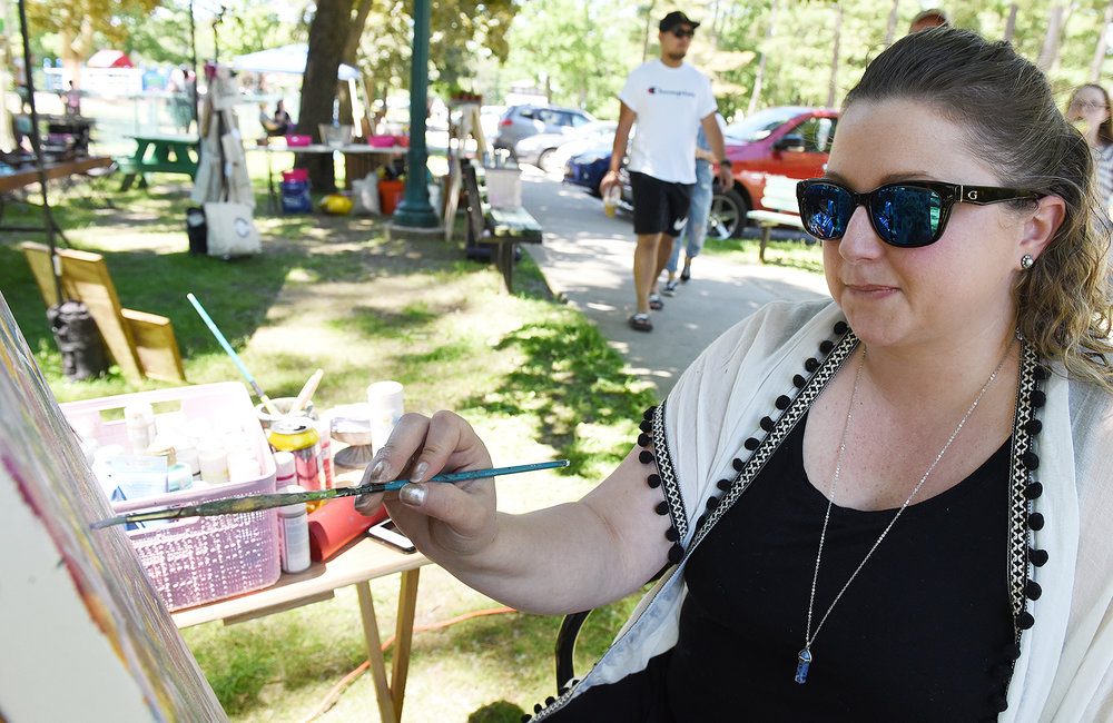 ERICA MILLER/GAZETTE PHOTOGRAPHER   Kristin Lombard, of Troy and owner of Krilo Art, works on a piece that will be given away to a follower during the inaugural Discover Schenectady's Summer Kick Off Event at Music Haven in Schenectady's Central Park in Schenectady on Saturday, June 7, 2019.