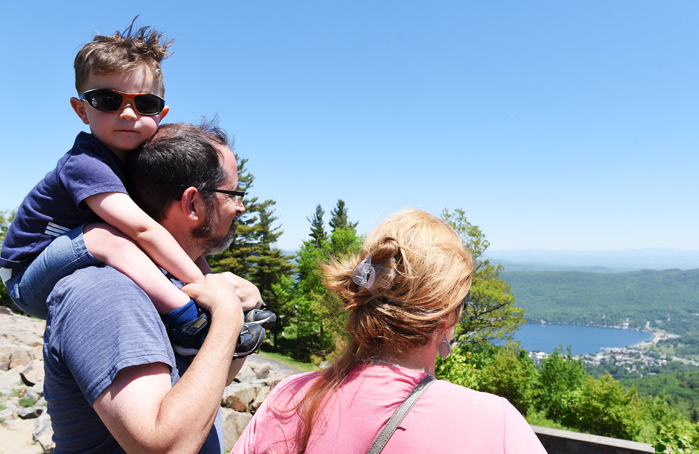 ERICA MILLER/GAZETTE PHOTOGRAPHER   Brady and Arcangela Chapman, of Delmar, and their son Aiden, 2-years-old, take in the views from the top of Prospect Mountain for views of Lake George in Lake George on Sunday, June 9, 2019.