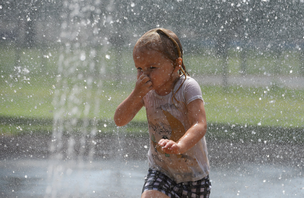 ERICA MILLER/GAZETTE PHOTOGRAPHER   Olivia Green, 3, cools off in the water spouts at East Side Rec on a hot and humid day in Saratoga Springs on Friday, July 19, 2019.