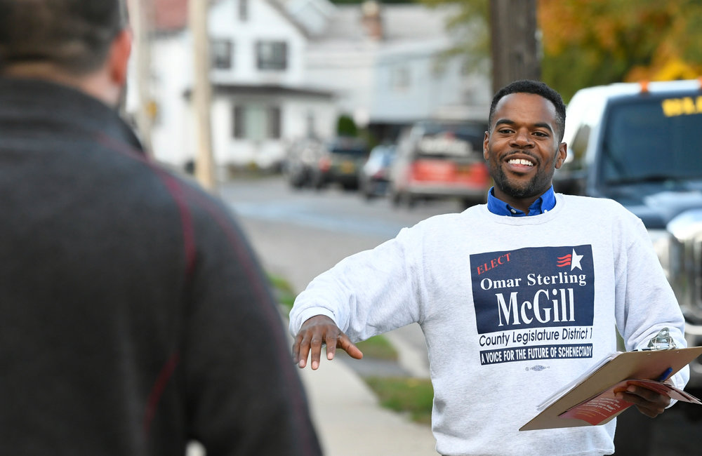PETER R. BARBER/GAZETTE PHOTOGRAPHER Schenectady County Legislature candidate Omar Sterling McGill approaches Matt March on Eleventh Street in Bellevue Wednesday, October 23, 2019.