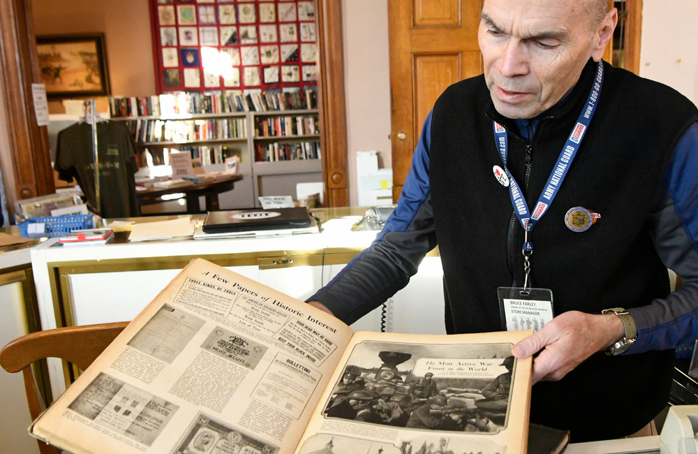 PETER R. BARBER/GAZETTE PHOTOGRAPHER New York State Military Museum store manager Bruce Farley opens a World War I book in Saratoga Spring Wednesday, November 13, 2019.