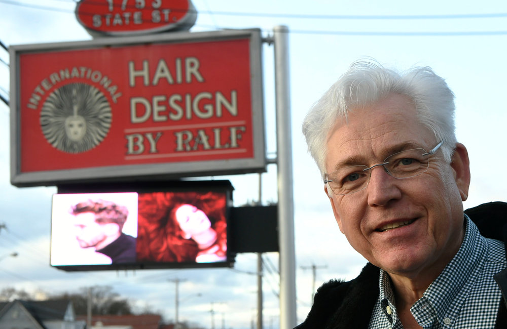 PETER R. BARBER/GAZETTE PHOTOGRAPHER Ralf Torkel, owner of Hair Design by Ralf stands with his business sign in the background Friday, November 22, 2019.