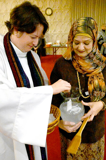 """MARC SCHULTZ/GAZETTE PHOTOGRAPHER During the Interfaith Thanksgiving Service held Sunday evening at the Unitarian Universalist Society of Schenectady, Rev. Sara Baron of the United Methodist Church of Schenectady, and Humera Kahn, Interfaith Coordinator Islamic Center of the Capital District, both dissolve  """"Authentic Truths"""" that are thoughts of thanksgiving and greivegiving that gathering attendees had written down on paper."""