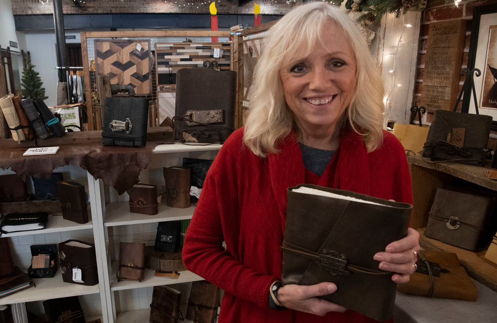PETER R. BARBER/GAZETTE PHOTOGRAPHER Handmade leather journals by MGD Designs owner Marilyn DeMartino at the Clinton Street Merchantile Wednesday, November 20, 2019.