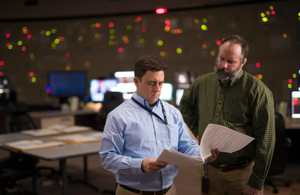 PHOTO PROVIDED Ray Joyce, left, director of National Grid's Eastern Regional Control Center, confers with Regional Operator Chris White.
